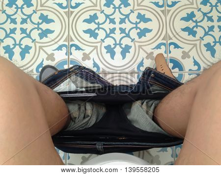 Top view of man sitting on toilet
