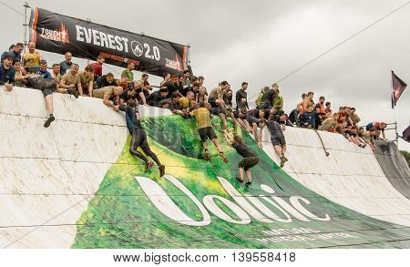 Grantham Leicestershire/UK - May 21, 2016: Participants hit the slippery wall at the Everest 2.0 obstacle at the 2016 Tough Mudder extreme sports charity competition at Belvoir Castle.