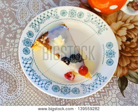 Piece of sweet cake with berries and cream sauce on a plate on a rustic kitchen.