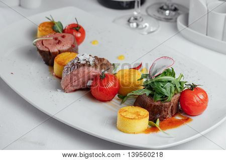 Veal With Sauce, Greens And Marinated Tomatoes On A White Plate