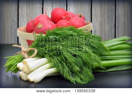 Healthy diet food. red radishes green onions and dill on wooden table.Spring. Vitamins. Organic vegetables. Country style .