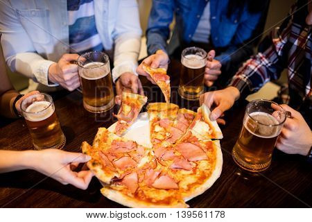 High angle view of friends with beer mug and pizza on table in bar