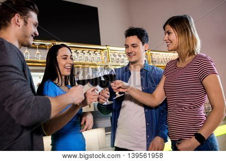 Cheerful young friends toasting wine at bar