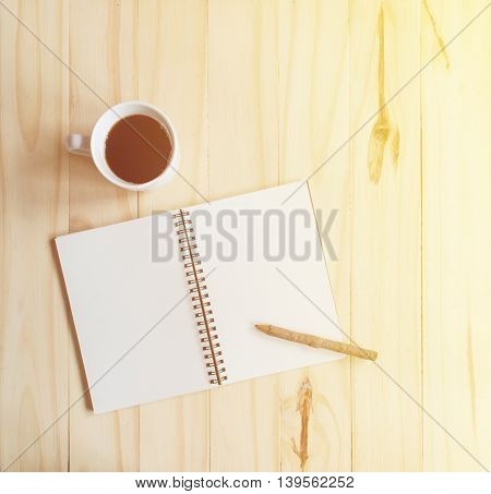 notebook and pencil on wooden table with morning sunlight