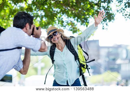Man photographing cheerful woman in city on sunny day