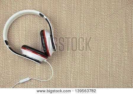 Comfortable soft earphones. Headphones on a rough fabric background. Listen to music. Melody. Top view. Country style. relaxation time.