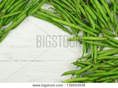 Green beans on a light wooden background. Top view. Agriculture. Horticulture. Country style. Crop.