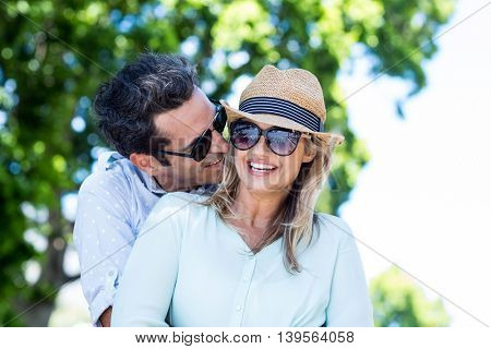 Happy couple embracing while standing against trees