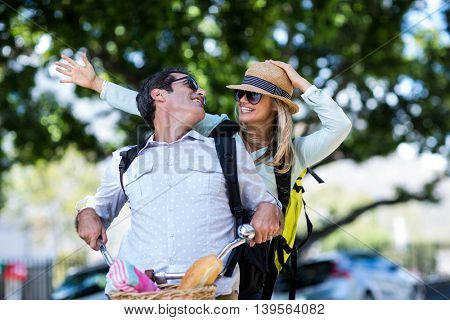 Couple smiling while riding bicycle on street in city