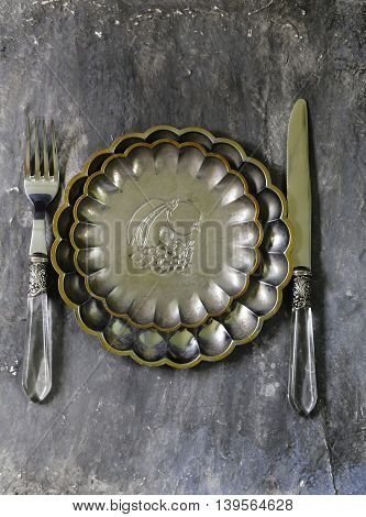 vintage cutlery and a plate on a gray background