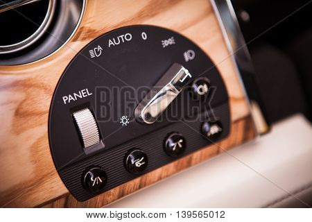Close up shot of the headlights button in a car.