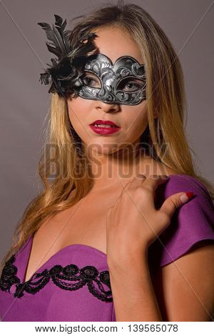 fashion young woman with a mask on a grey background