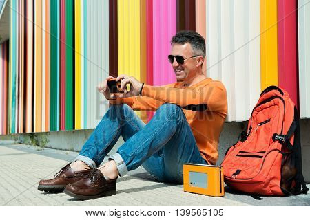 Street fashion. Male outdoor portrait. Man sitting near colored urban wall in jeans and orange sweater with backpack and using smart phone. Selfie.