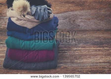 stack of folded woolen gray, green, blue and red clothes on wooden background with copy space, retro toned