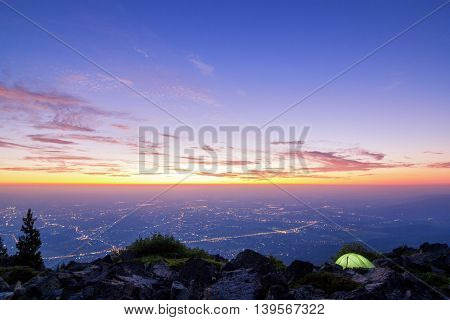 camping in the mountains and beautiful sunrise over the city in Europe