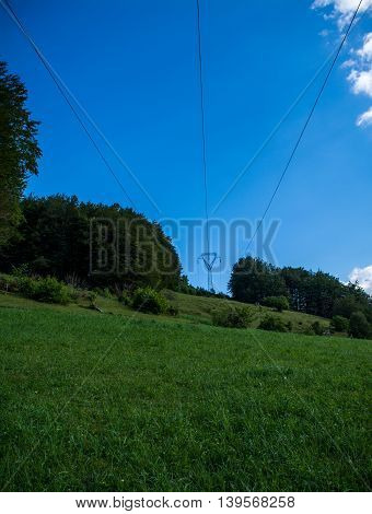 Power transmission lines at the end of beautiful green field