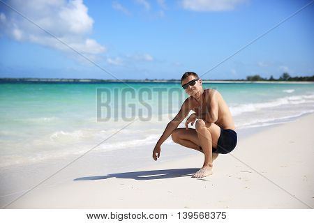 A guy on a paradise beach in sunglasses and shorts on a background of turquoise lagoon