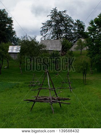 Object on green field with barns in the back