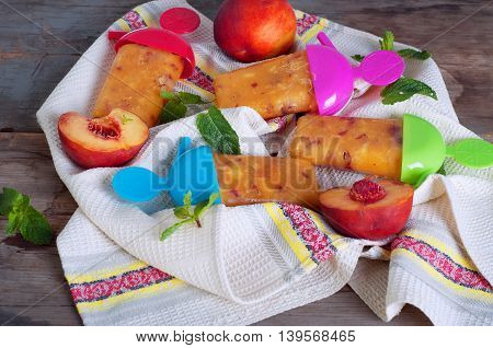 Peach ice lollies with colores sticks on a kitchen napkin with mint leaves