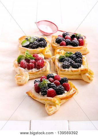 Puff pastry cakes with cream filling and berry topping