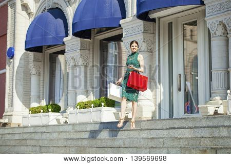 Young beautiful brunette woman with some shopping bags, outdoors summer street