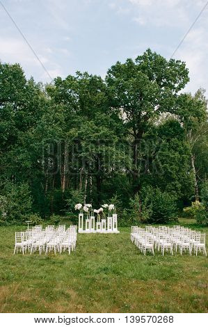 wedding ceremony in a beautiful garden. white chairs and mirrored tables. Glass vase with flowers calla lilies and white amaryllis