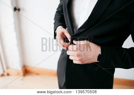 Making business look good. Close-up of man buttoning his jacket while standing against grey background