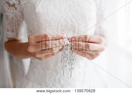 earring in bridal hands. Beautiful wedding accessories