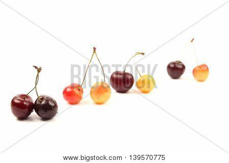 cherries lying in pairs on white background