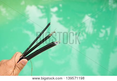 Optic fiber cable in hand with swimming pool background.