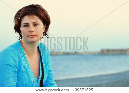 Portrait of beautiful young woman in blue shirt on a sea coast with space for text