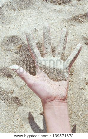 sand on hand and finger of the girl