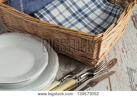Items for table setting. Canteens napkin in a wicker basket, plates, forks and knives on a light wooden table.