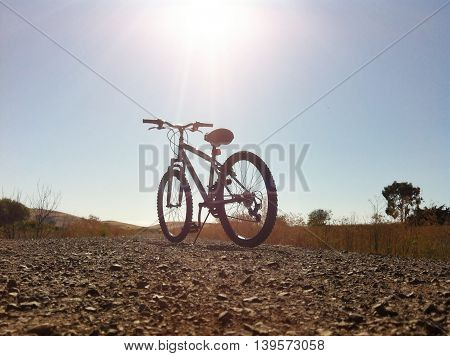 Bicycle in a middle of the road at the countryside against sun and sky
