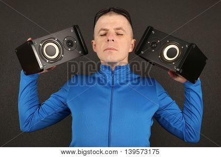 man with eyes closed holding two audio speakers