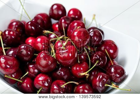 Close up view of a bowl of ripe cherries. Selective focus on front middle cherry.