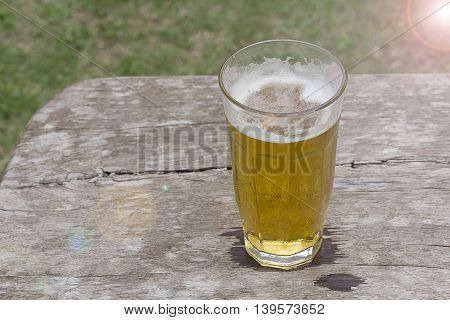 Glass of beer with light flare on table