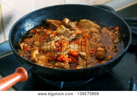 Cooking pork with carrot and onion on stove