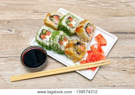 different rolls on a plate with ginger and soy sauce. wood background - horizontal photo.
