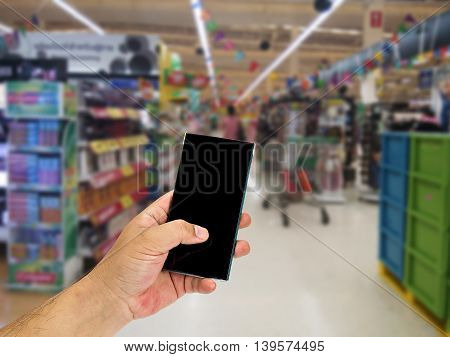 Man hand holding smart phone over blurred shopping center or super market background.