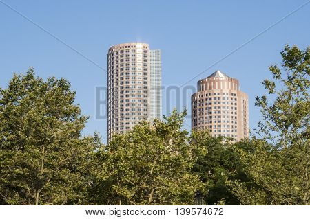 Tallest buildings on Rowes Wharf skyline towering over trees on Fan Pier along Boston waterfront