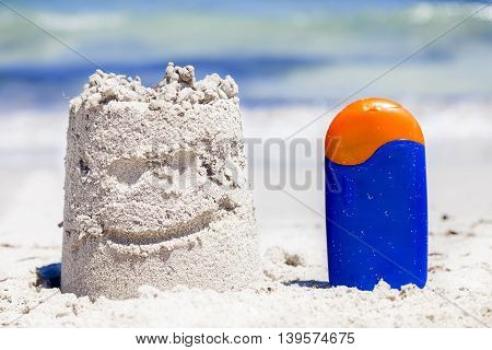 Small Sand Castle And Bronzing On The Seashore During Summer