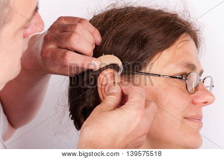 Doctor inserting a hearing aid into the ear of a woman patient