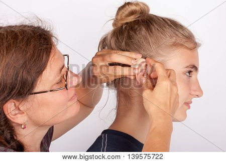 Audiologist fitting a young woman patient with a behind-the-ear hearing aid