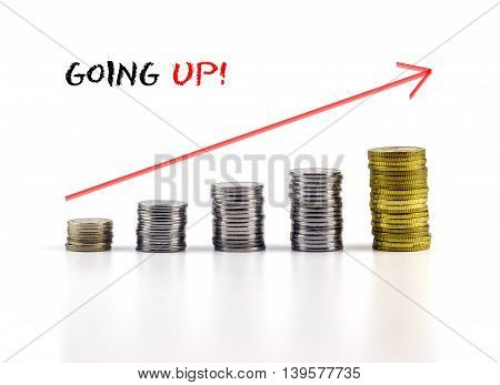 Conceptual Image. Stacks Of Coins Against White Background With Red Arrow And Going Up Words.