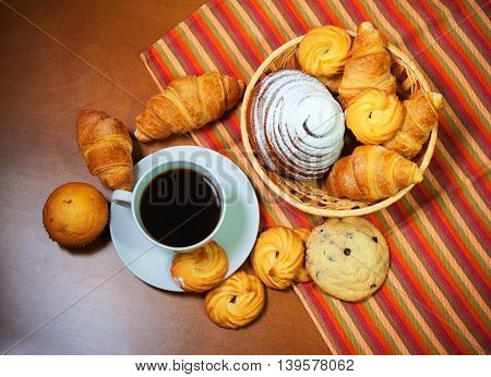 Cookies pastries and coffee cup on wooden background