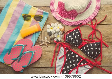 Beauty colorful bikini and accessories on wooden floor