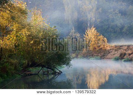Beautiful Autumn Fall landscape over foggy misty lake