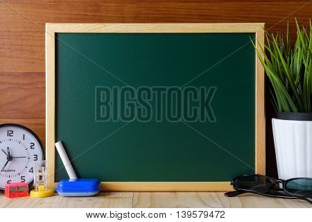 Blank Green Chalk Board On Top Of Wooden Table.