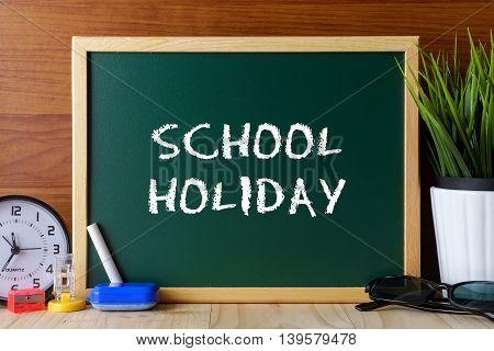 Words School Holiday Written On Green Chalk Board On Wooden Table.